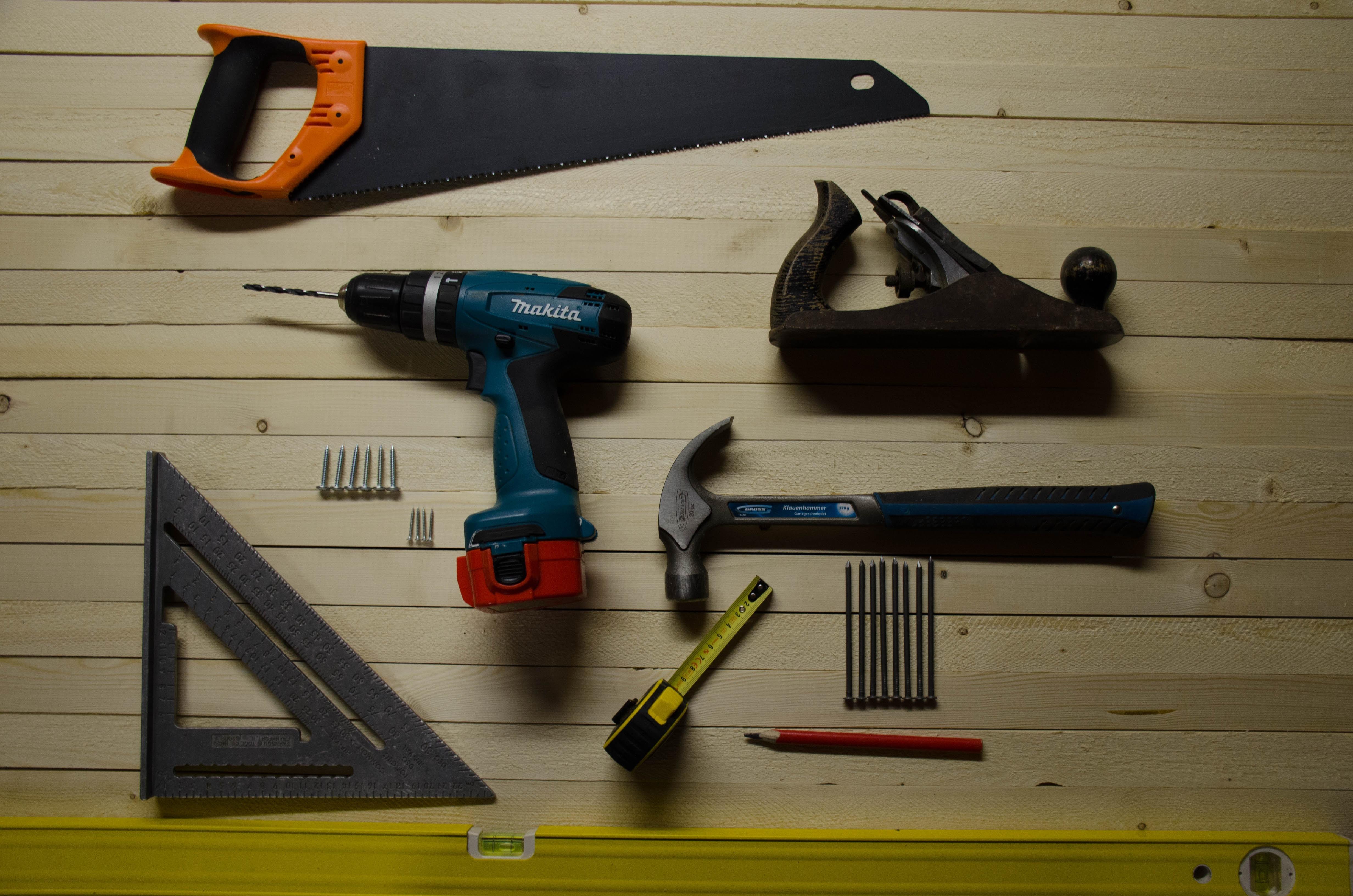 outils de bricolage sur un sol en bois avec scie equerre perceuse marteau vis crayon metre