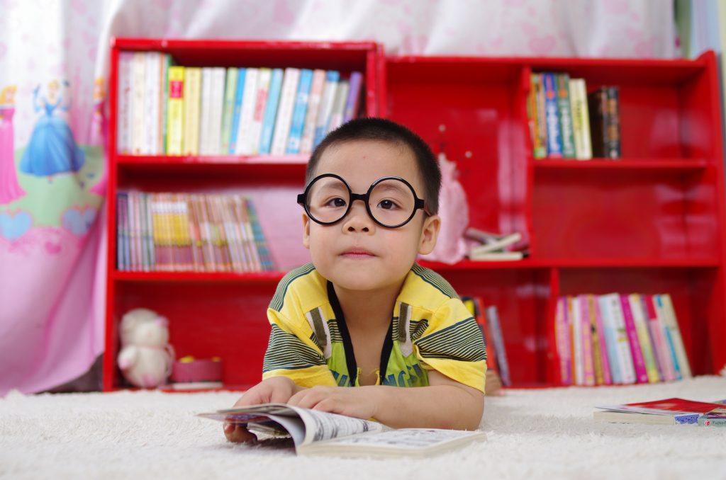 Un enfant qui lit devant une étagère dans sa chambre
