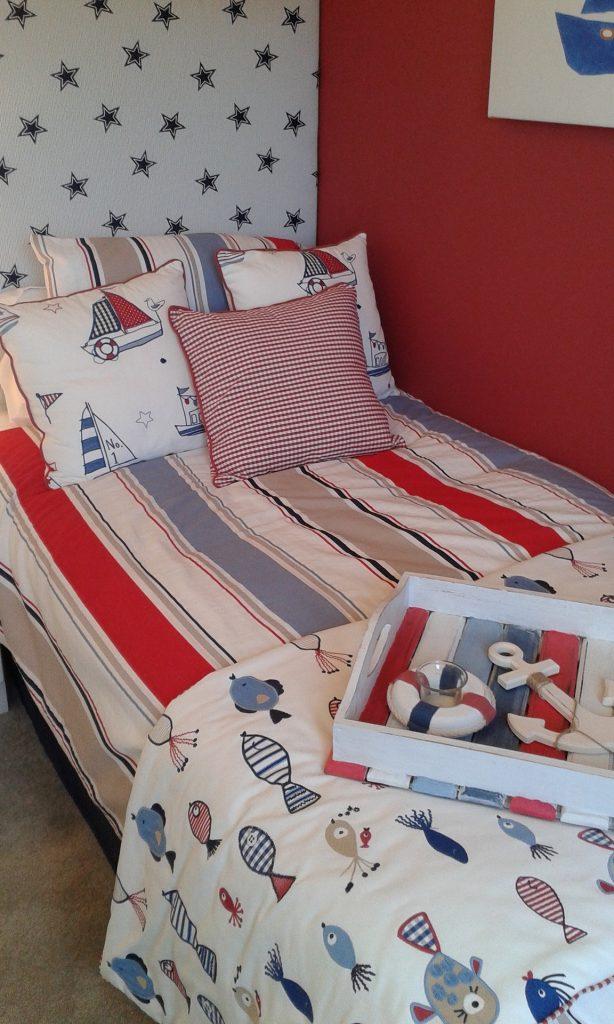 Une chambre d'enfant rouge bleure et balnche sur le thème de la mer