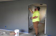 Peintre qui peint les murs d'une pièce en gris
