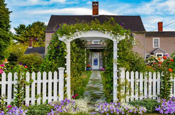Entrée d'un jardin avec barrières blanches fleuries