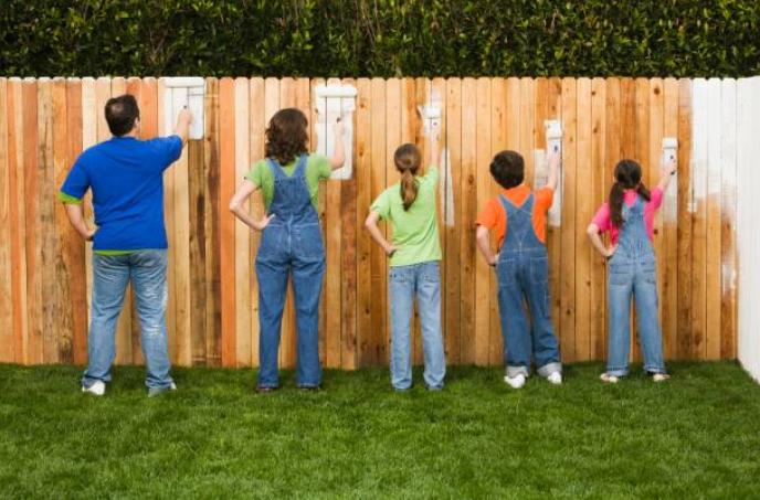 Famille qui peint une clôture en bois dans un jardin