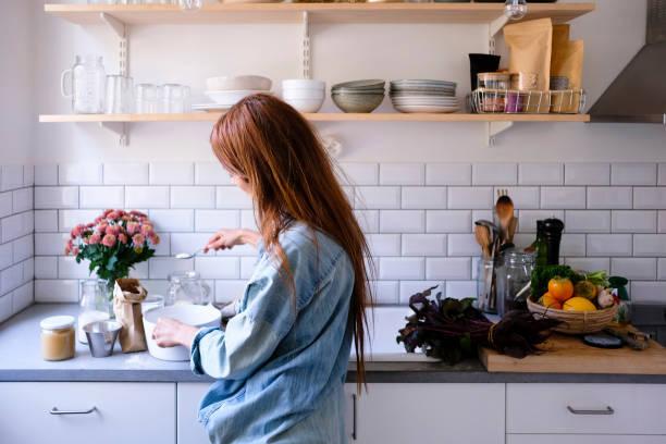Jeune femme en train de cuisiner dans sa cuisine bien aménagée