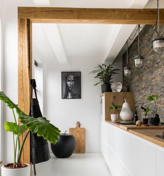 cuisine dans les tons blanc et ois avec mur en pierre et plante