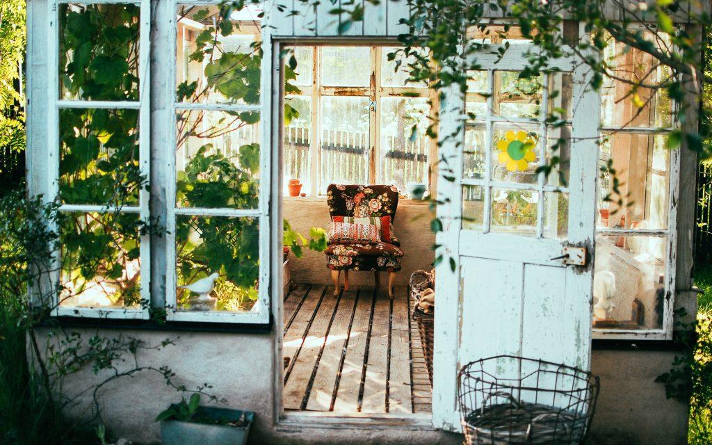 Abri de jardin et serre avec chaise et plantes