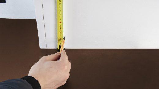 personne qui mesure une plinthe avec un mètre